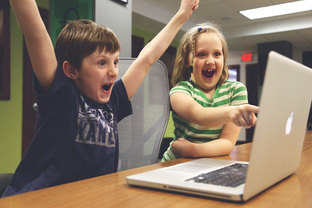 2 Kinder Jubeln vorm Computer